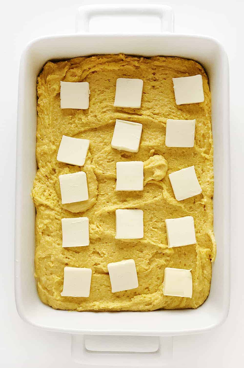 Pan of Sweet Cornbread Unbaked with Butter Pats on Top