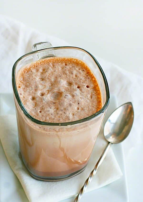 Glass of Frothy Chocolate Milk with Spoon