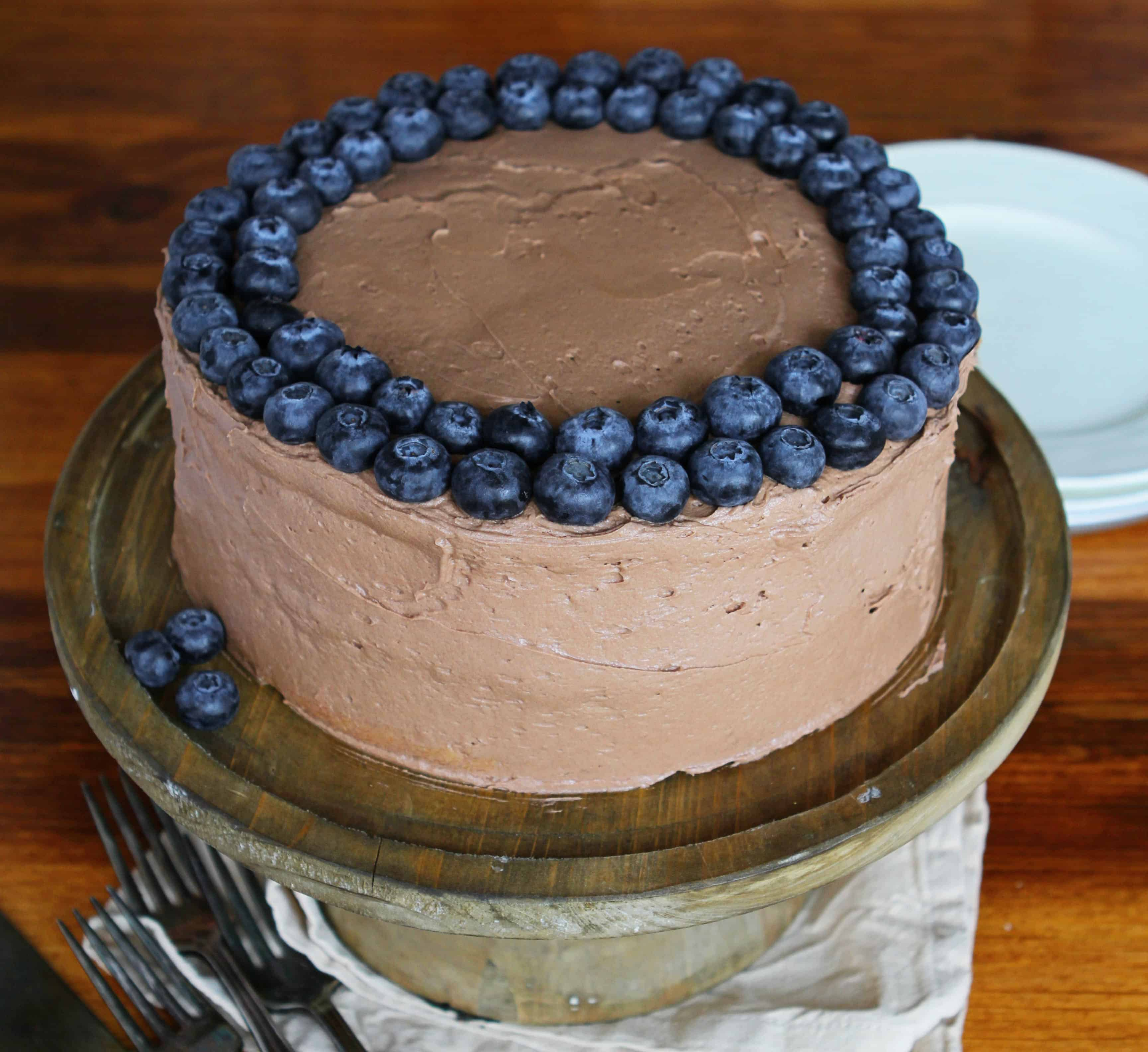 White Cake with Zucchini with Chocolate Frosting and Blueberries on Wooden Table with Plates in Background
