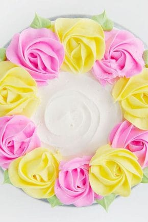 Create simple rustic lines in buttercream and then adorn with pink and yellow buttercream rosettes!