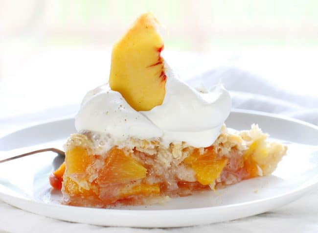 The perfect slice of peach pie with whipped cream and peach garnish!