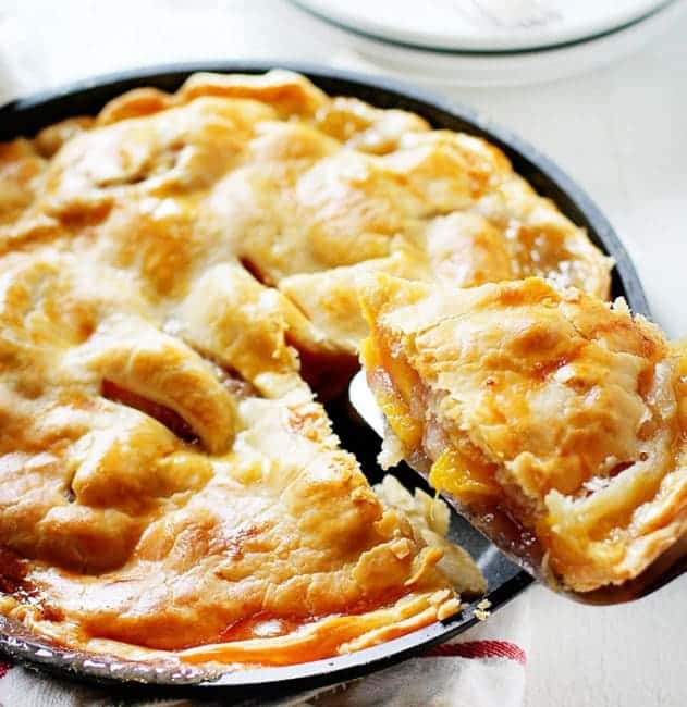 A perfectly baked and delicious peach pie with a piece headed for my plate!