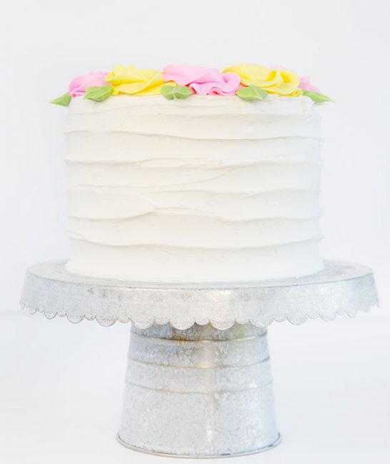Creating rustic lines on the sides of this cake make for a pretty compostion when adding simple pink and yellow rosettes to the top.