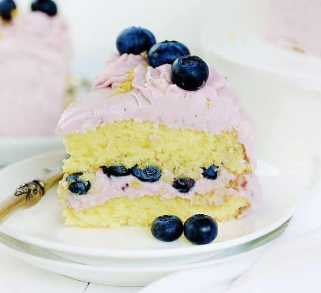 Slice of lemon layer cake with blueberry buttercream.