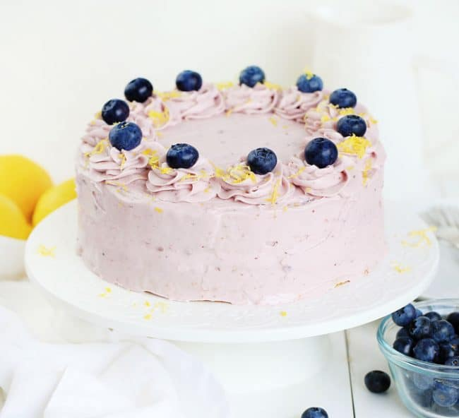 A lemon cake covered with blueberry buttercream and garnished with blueberries and lemon zest!