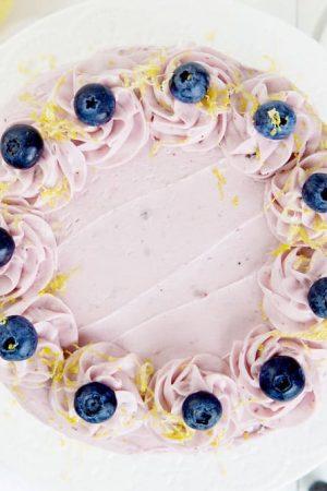 Overhead view of a lemon cake covered in blueberry buttercream, blueberries, and lemon zest.