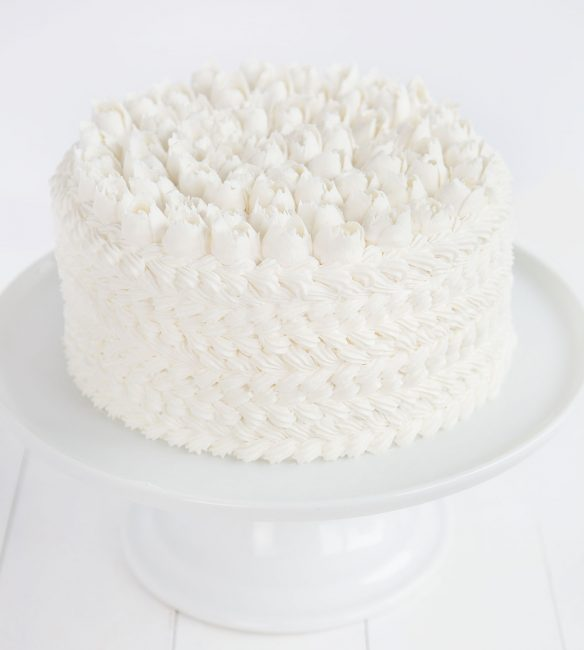 WASC Cake decorated with white buttercream with decorating tips on white cake stand.