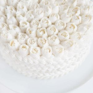 Cake covered in white butercream with Russian tip roses on top!