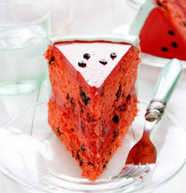 Slice of a cake that is decorated to look like a watermelon inside and out!