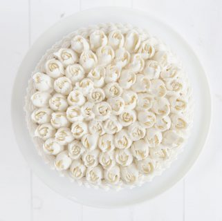 Overhead view of a cake covered in Russian tip roses with whipped vanilla buttercream.