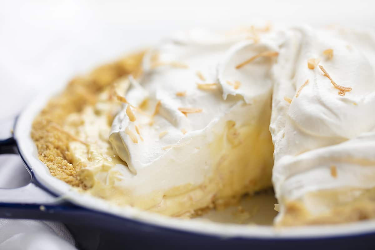Coconut Cream Pie with One Piece Removed in Blue Pie Pan