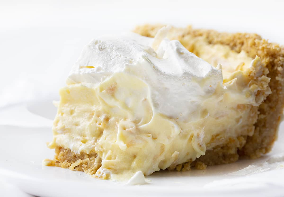 One slice of Coconut Cream Pie with a Bite Taken Out of It on a White Plate