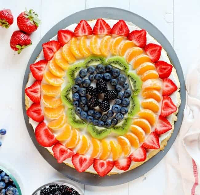 Amazing fruit displayed in a rainbow pattern over delicious sugar cookie and cream cheese frosting!