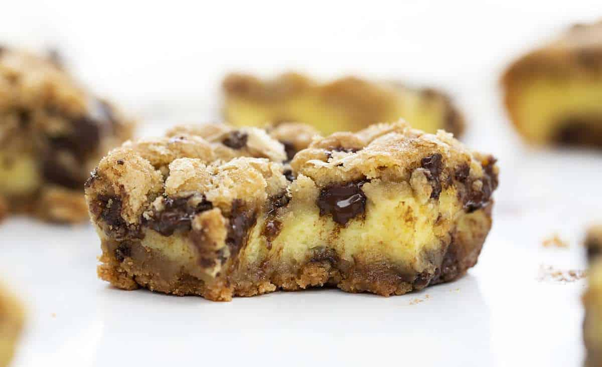 Chocolate Chip Cheesecake Bars Recipe With A Bite Removed Showing Melted Chocolate Inside