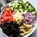 All the ingredients for the greek pasta salad in a large white bowl with grey napkin on the side