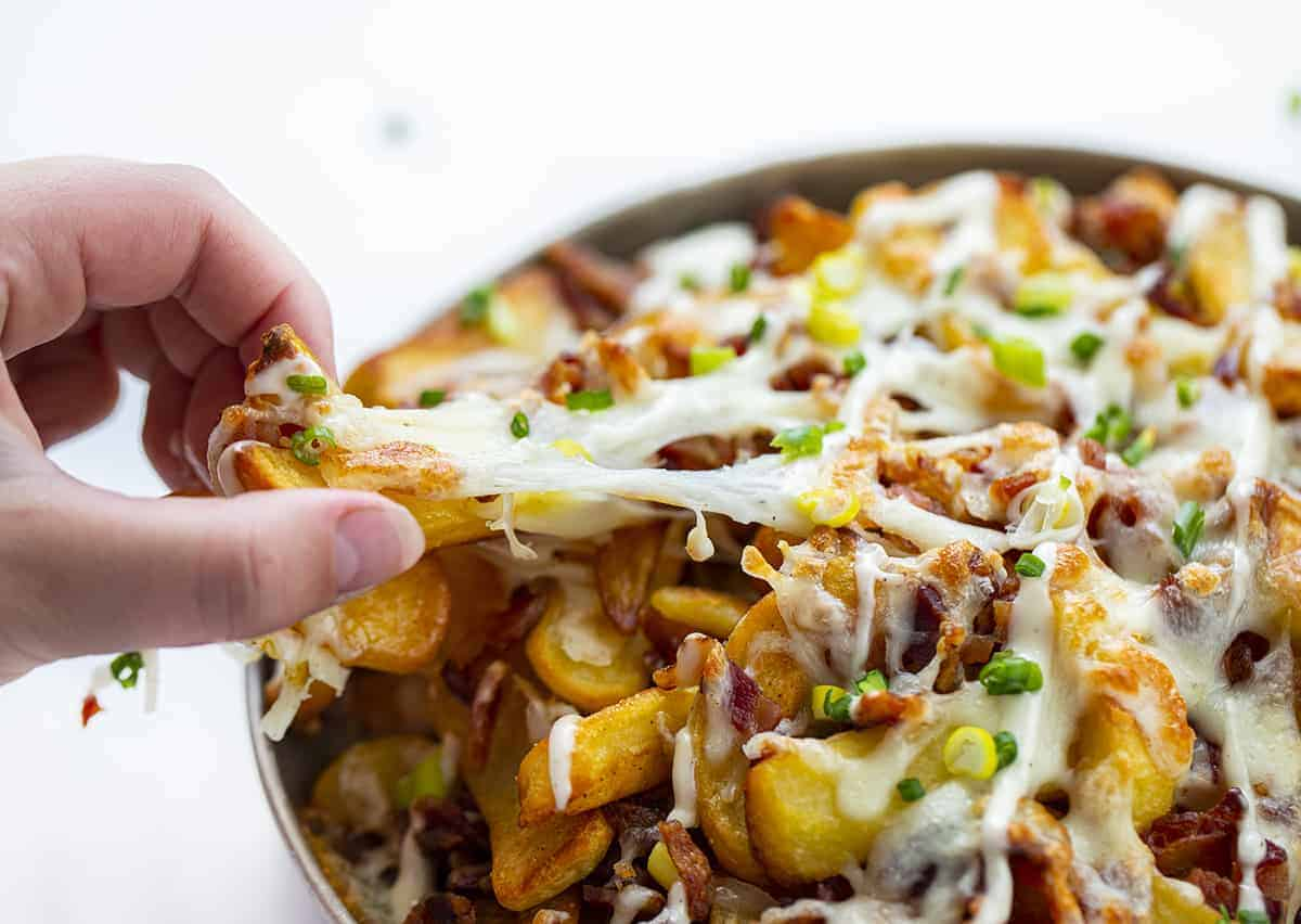 Loaded Cheese Fries Being Pulled with Hand Showing Stretchy Cheese