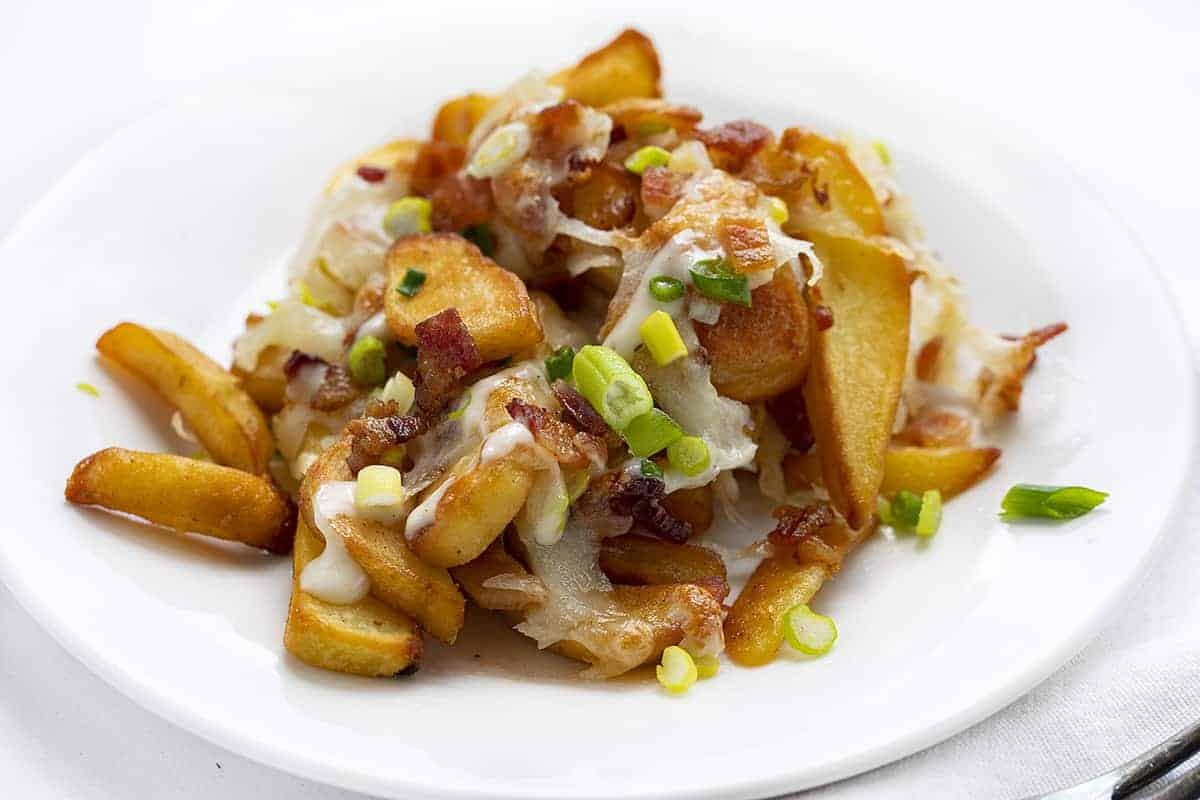 Plate of Cheese Fries Topped with Bacon, Cheese, and Scallion