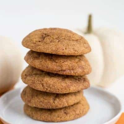 stack of pumpkin snickerdoodles on a white plate with white pumpkins behind them
