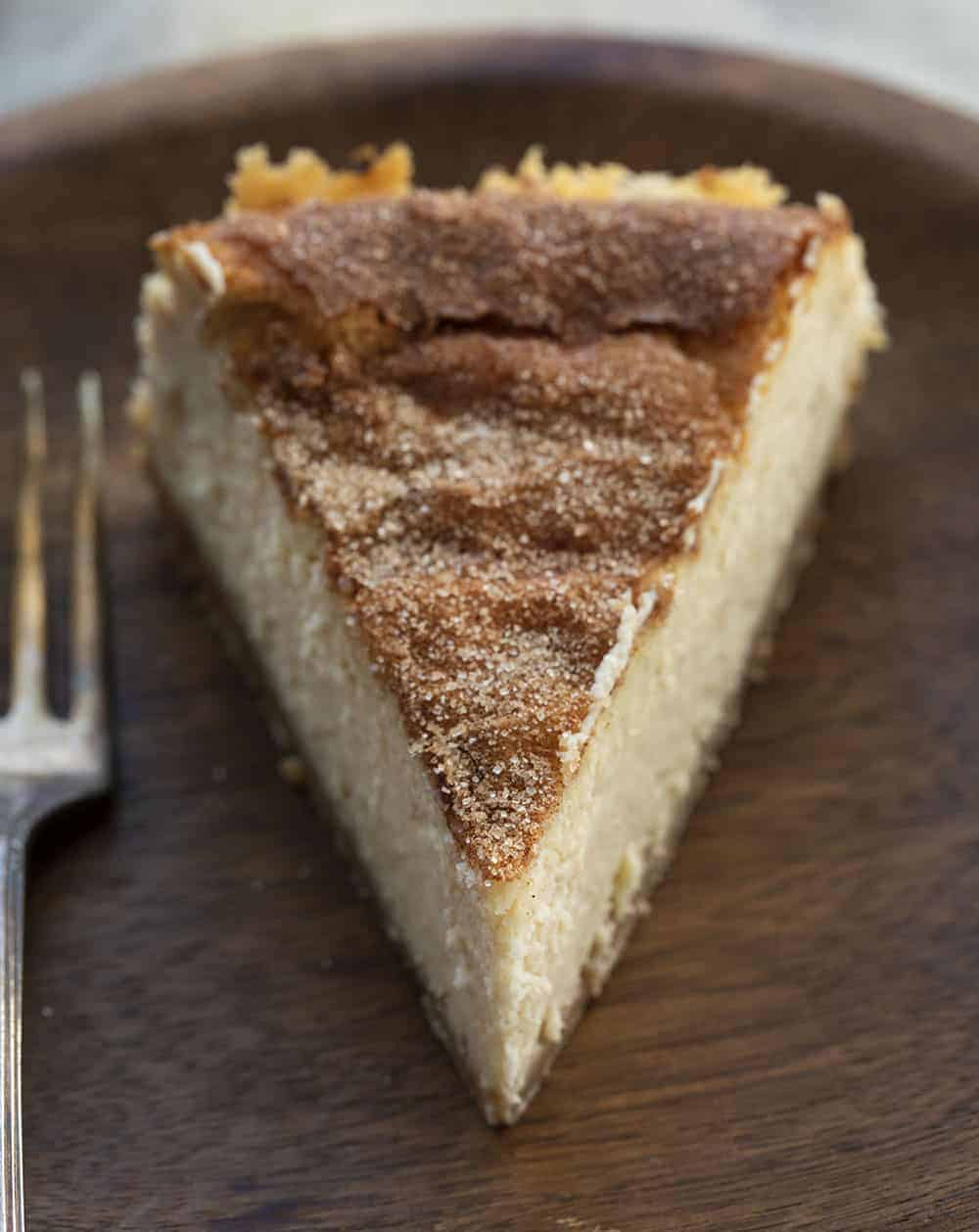 One Slice of Snickerdoodle Cheesecake on Wood Plate