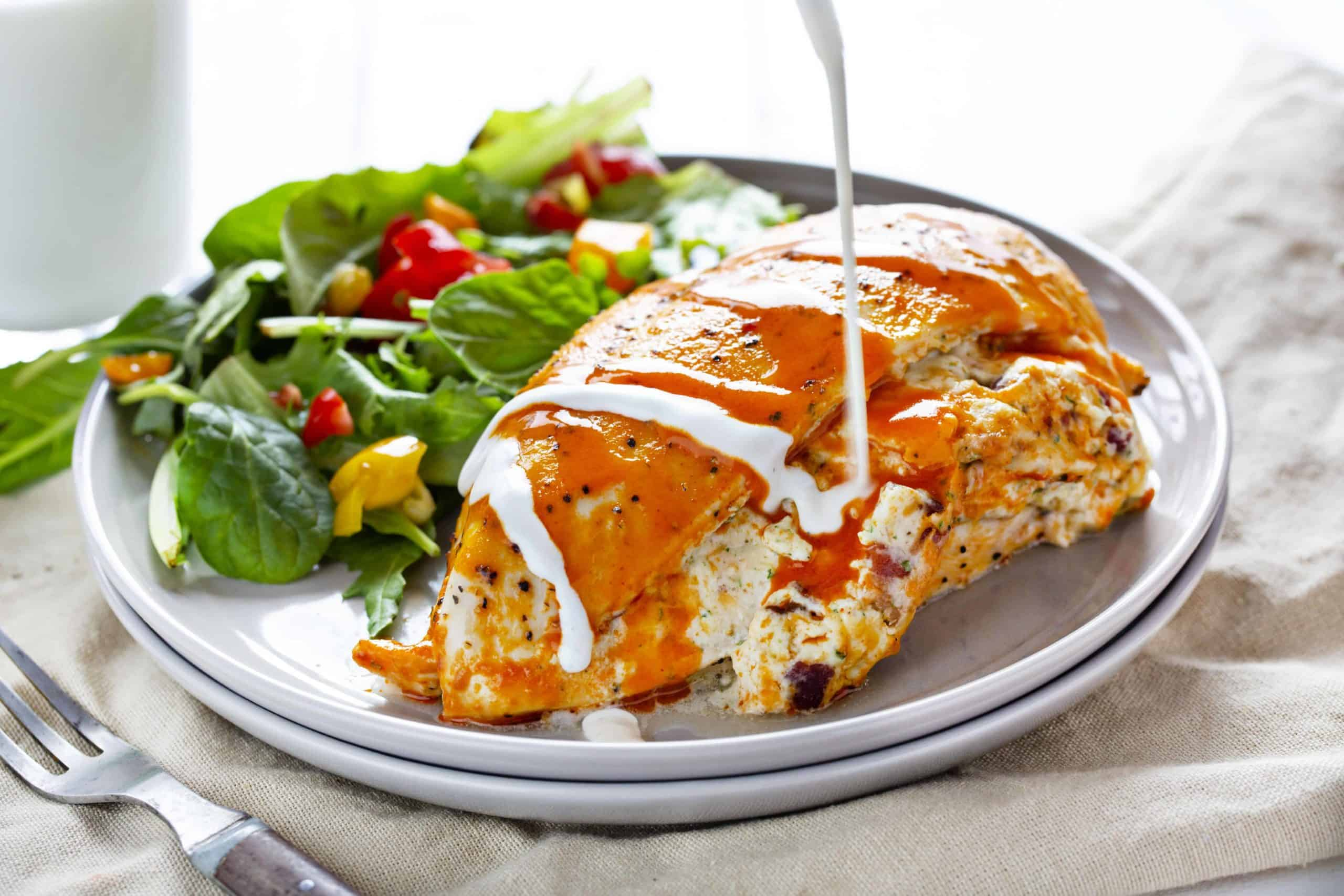 Spicy Buffalo Chicken with Ranch Being Drizzled