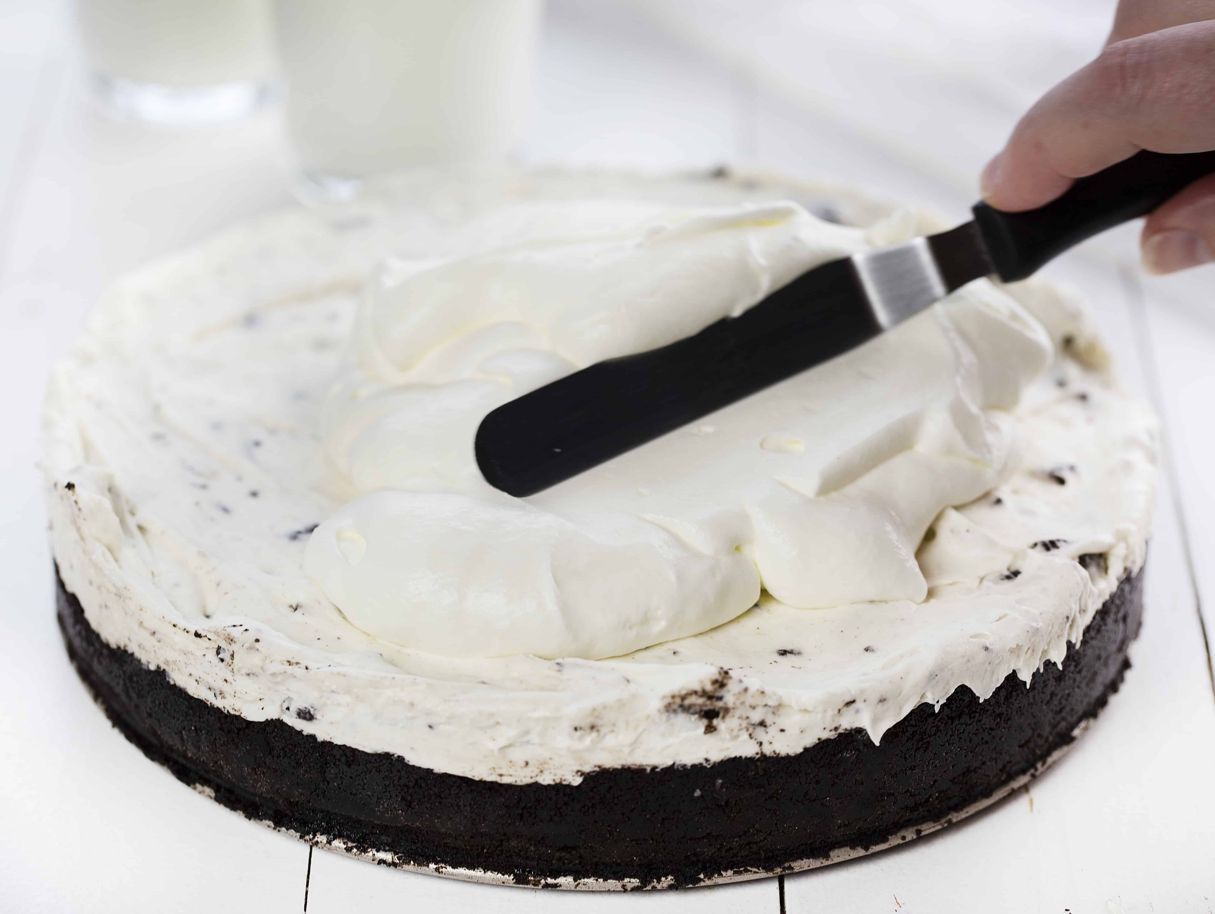 No Bake Oreo Cheesecake with Homemade Whipped Topping Being Spread on Top