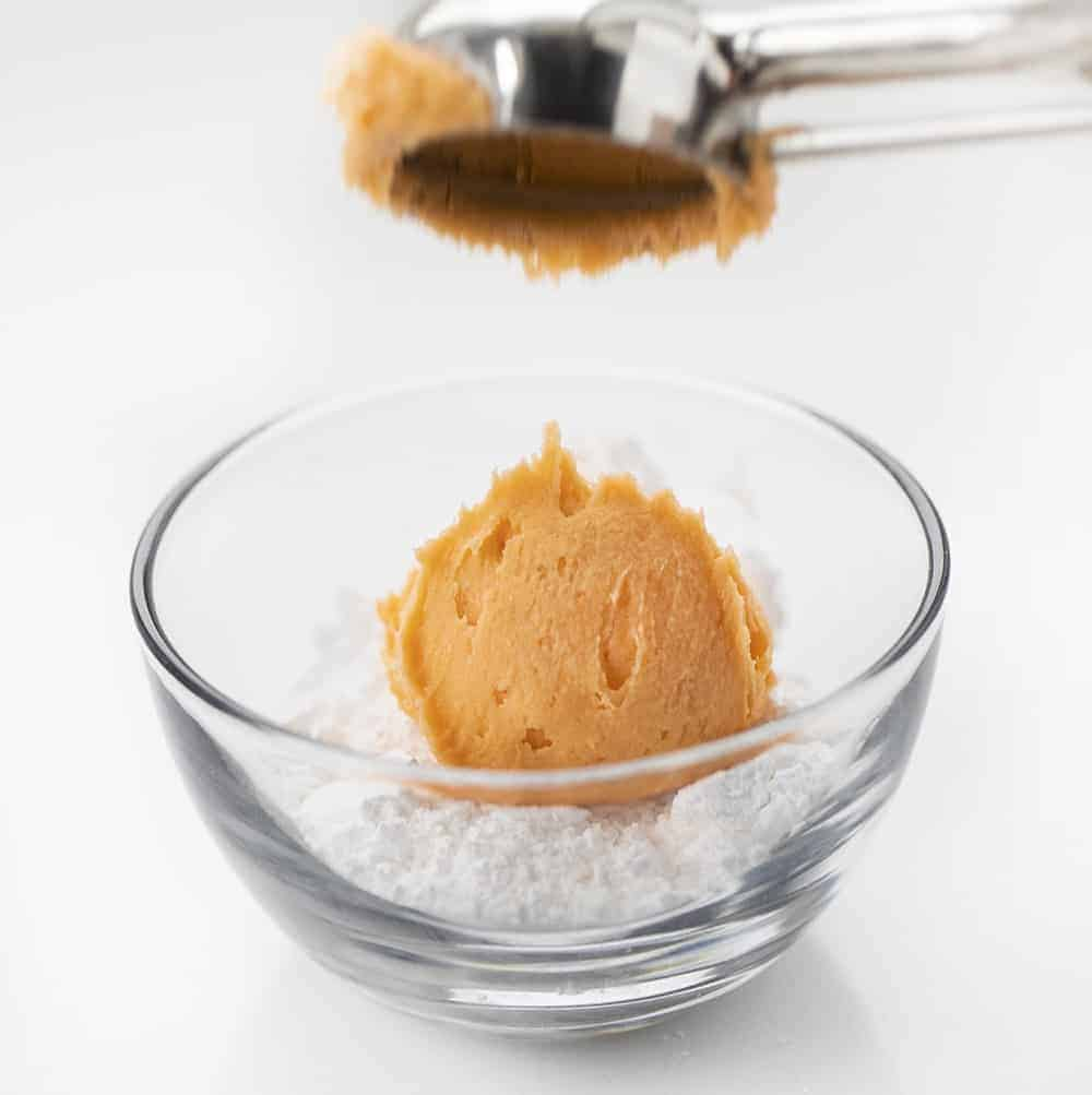 Orange Creamsicle Cookie Dough Being Dropped Into Bowl of Powdered Sugar