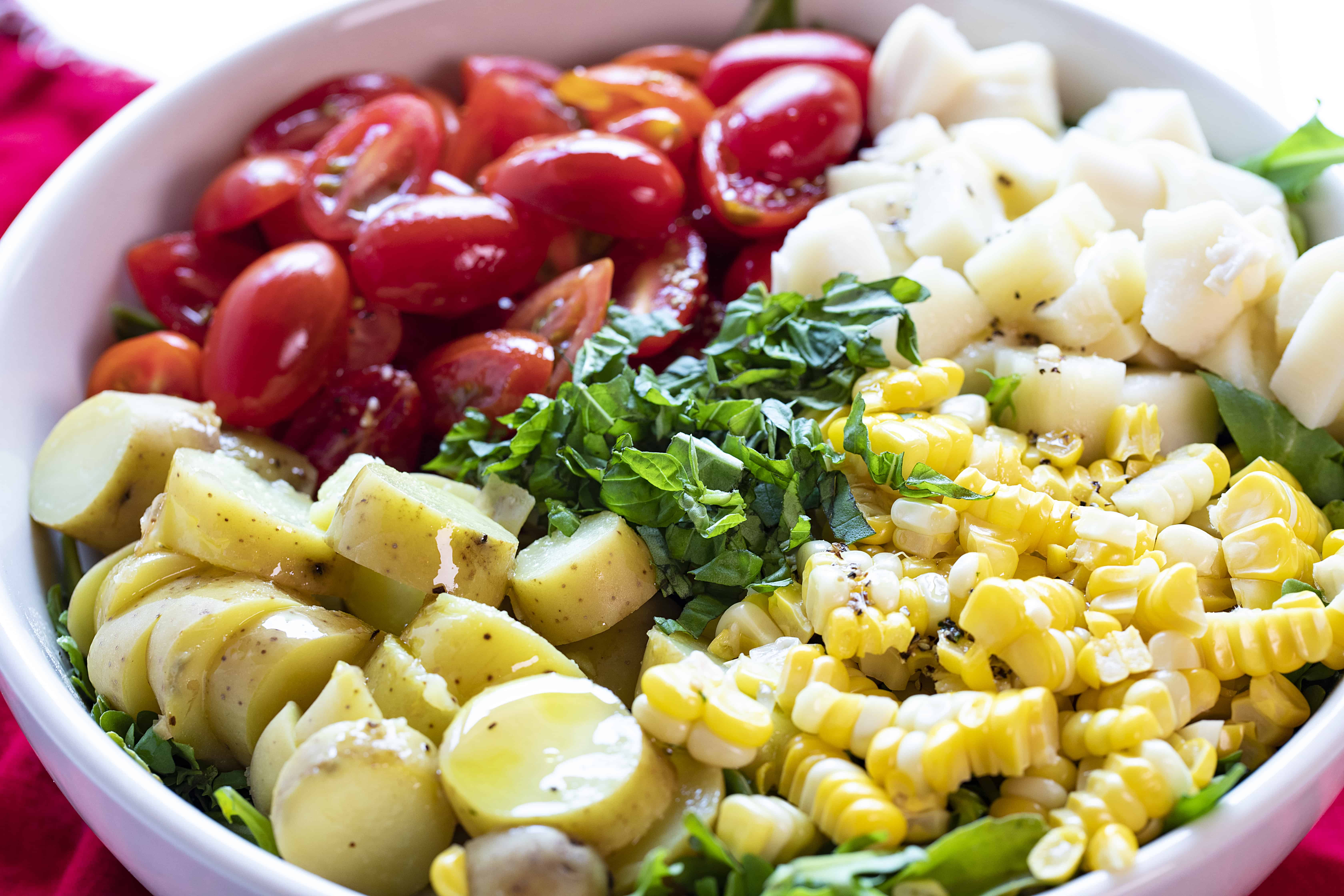 Beautiful Ingredients for the Perfect Summer Salad! Tomatoes, Corn, Potatoes all on Lettuce.