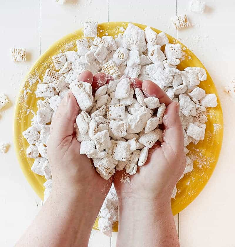 Hands full of Banana Pudding Puppy Chow