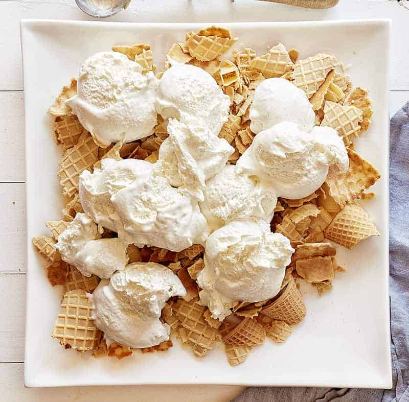 Waffle cone pieces topped with vanilla ice cream for Banana Split Nachos