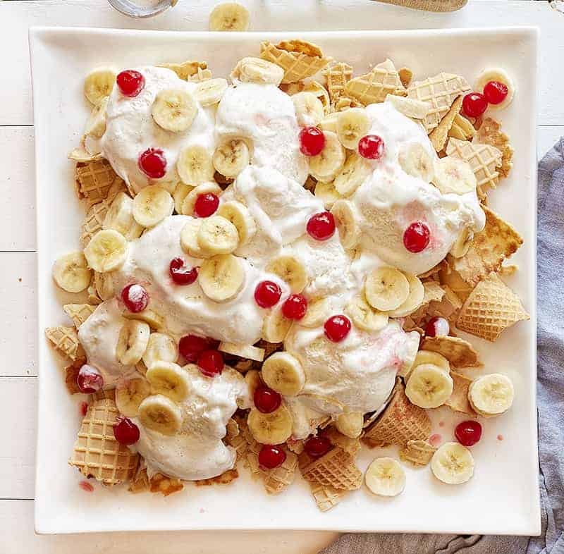 Topping Banana Split Waffles with bananas and cherries