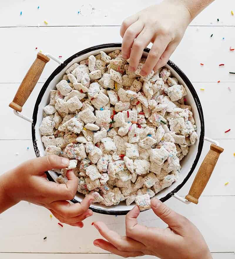 Childs hands Grabbing Birthday Cake Puppy Chow in a Bowl