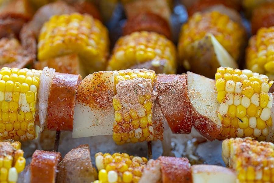 Cajun Shrimp Seasoning added to ingredients on a skewer