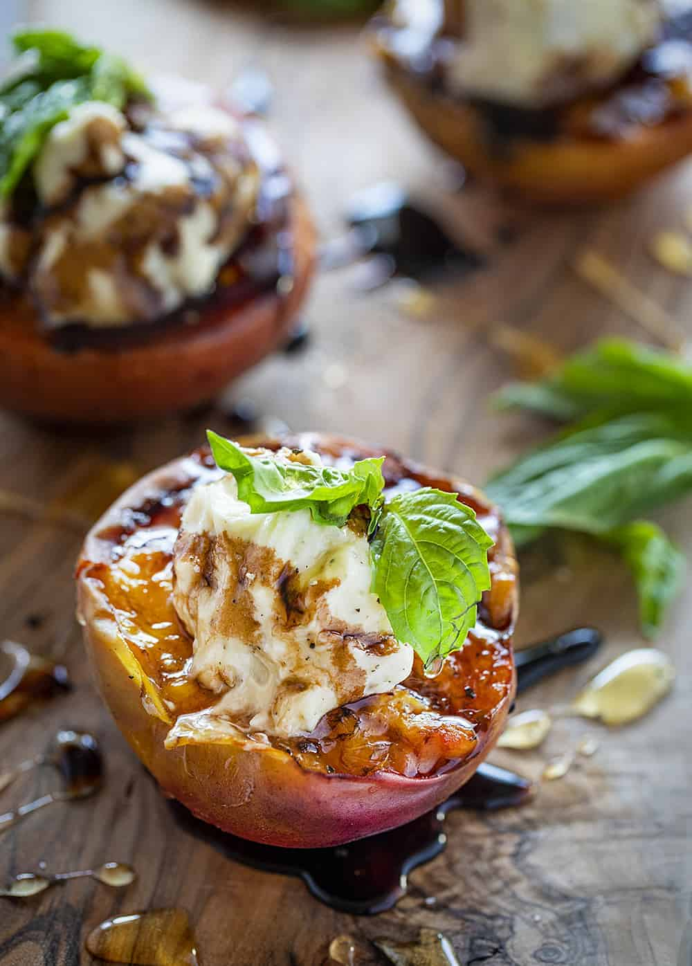 Grilled Peaches with Mascarpone and Balsamic Reduction topped with a basil leaf