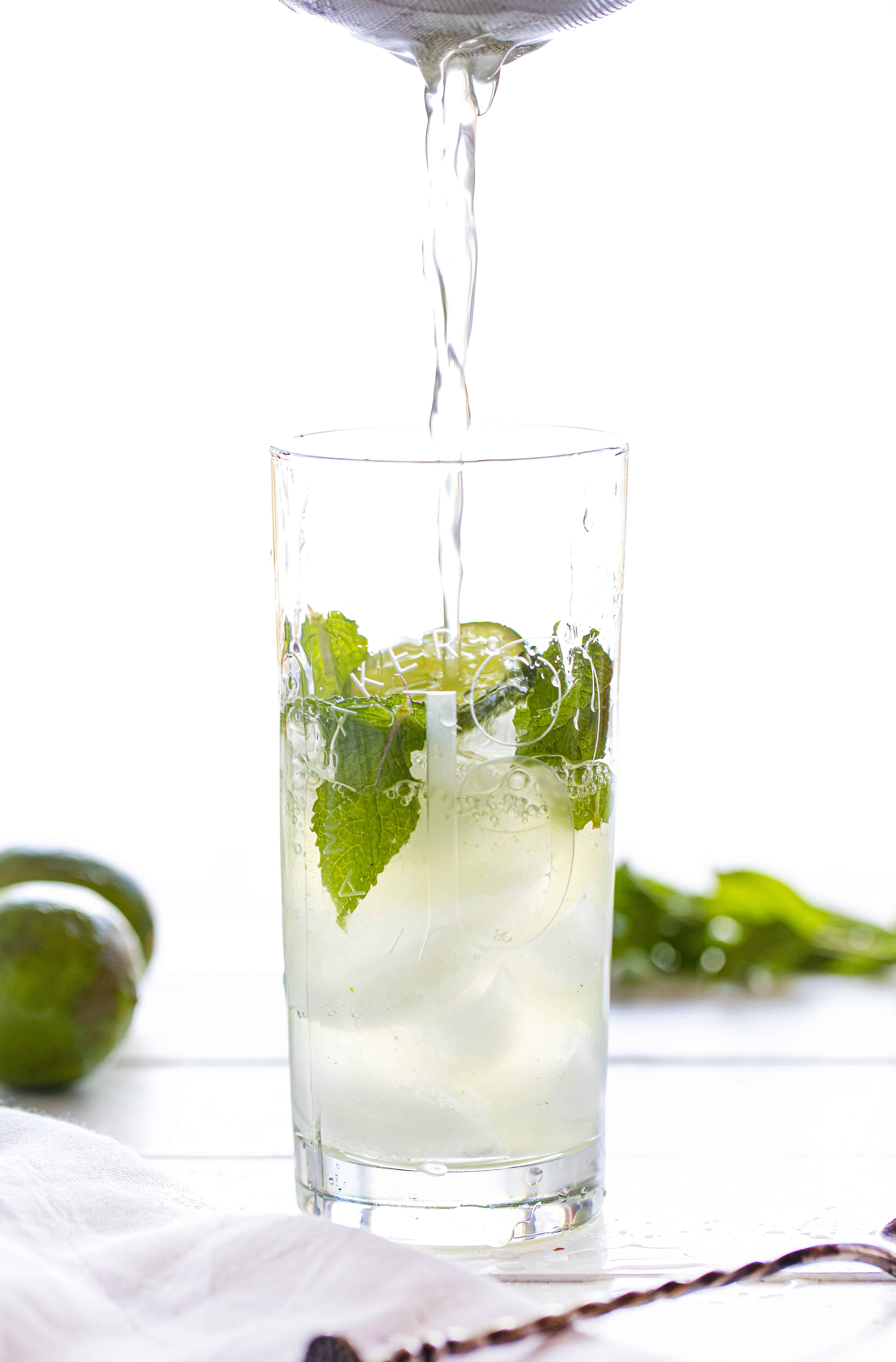 Straining Ingredients for Mojito Sangria Into a Glass