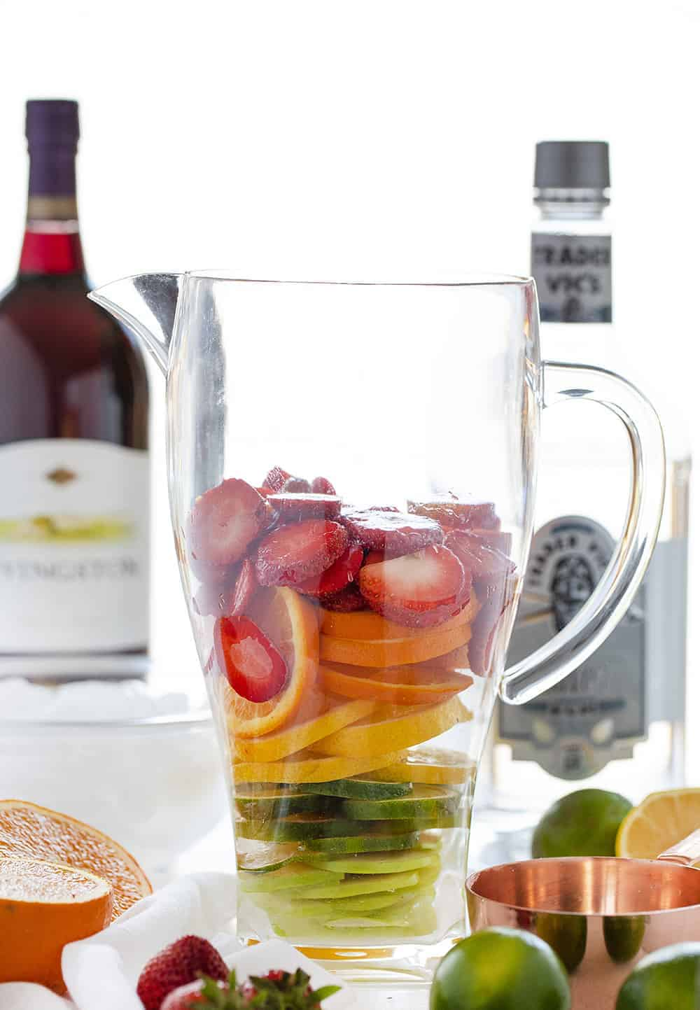 Piles of colorful fruit in a pitcher of Summer Sangria