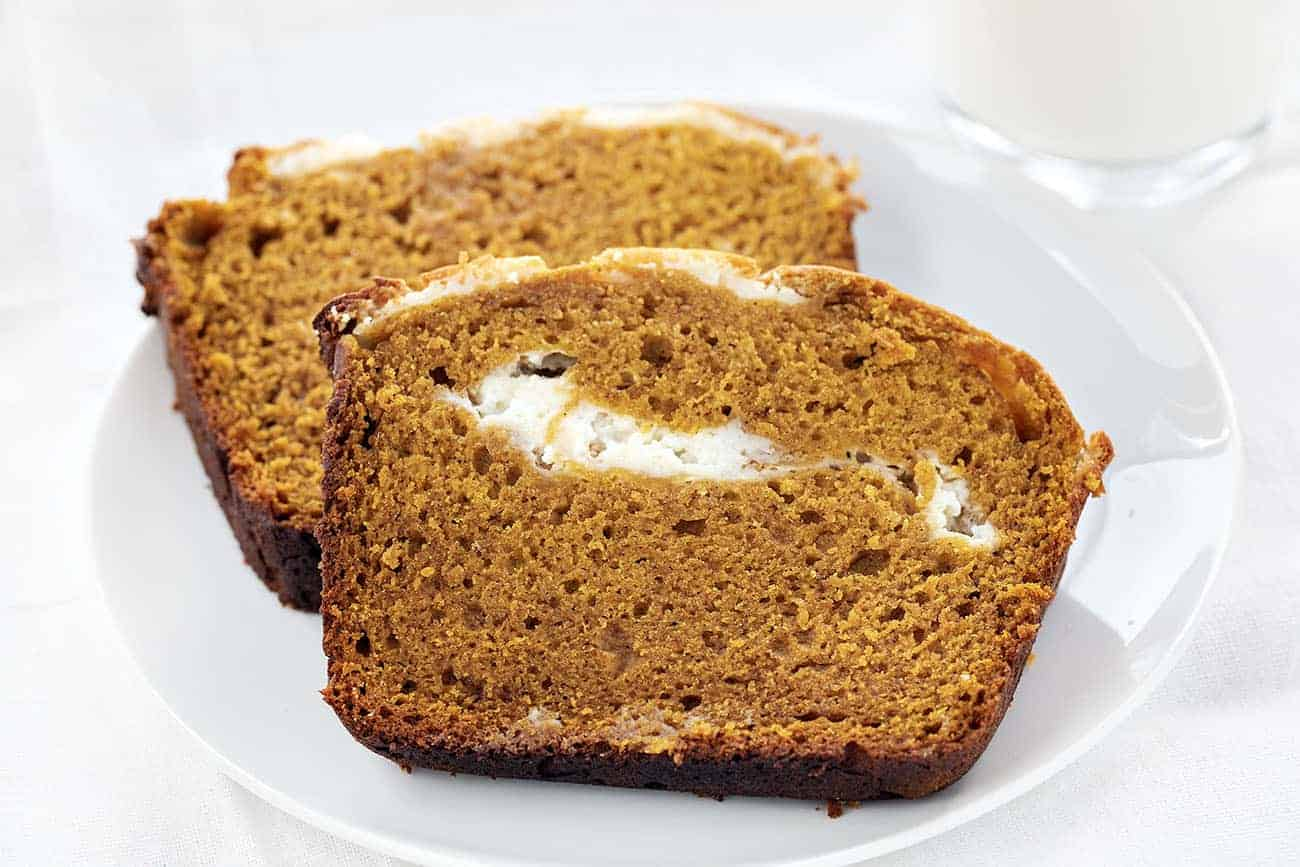 Two slices of Pumpkin Cream Cheese Swirl Loaf on a White Plate