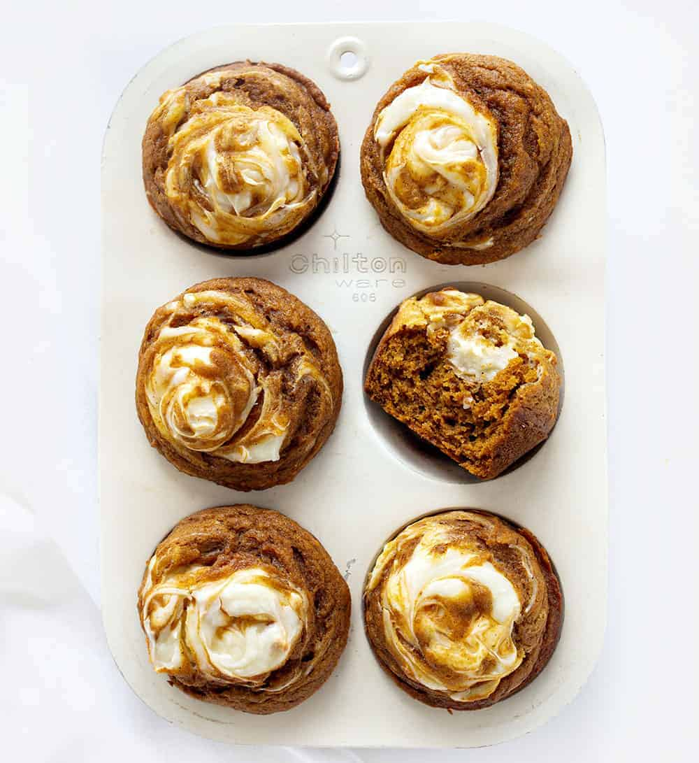 Overhead of Pumpkin Cream Cheese Swirl Muffins with One Halved