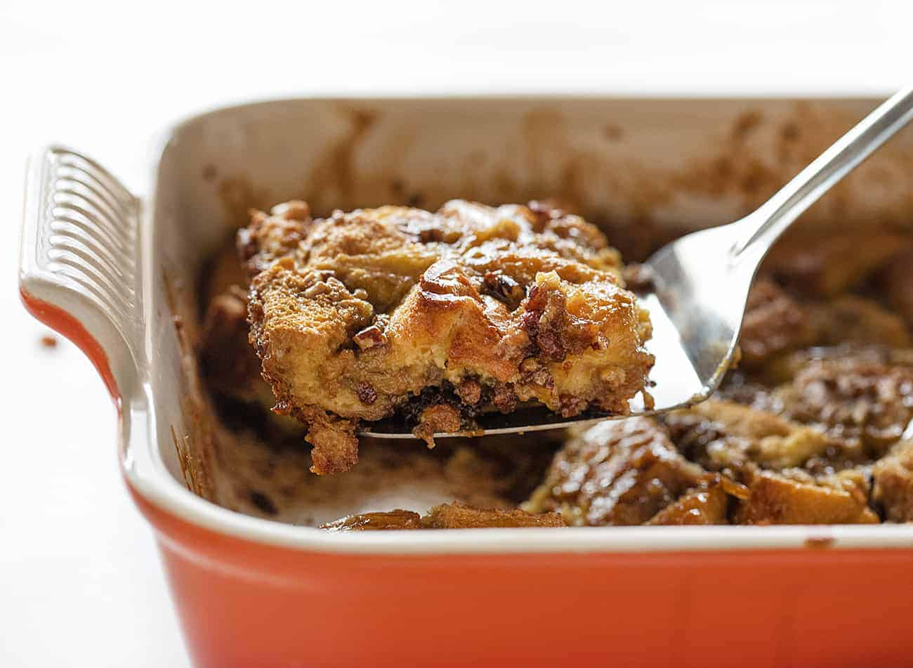 Serving one piece of Baked Pecan French Toast from a casserole dish