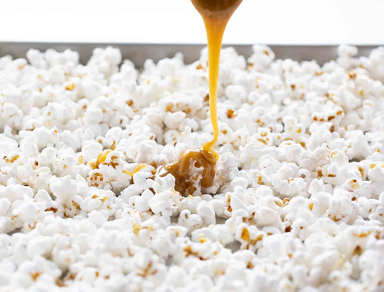 Pouring caramel over popcorn to make Caramel Corn