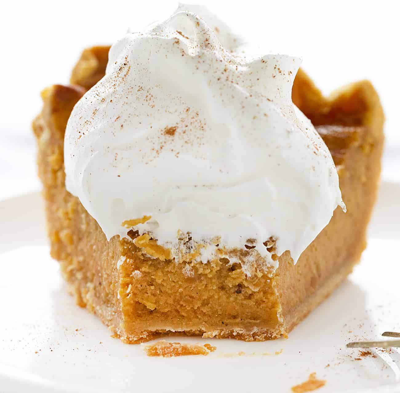 Bite Taken Out of Sweet Potato Pie with Whipped Cream on Top