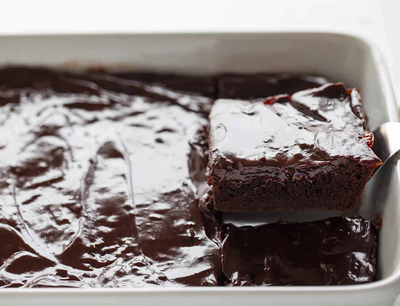 Cherry Brownies Being Taken Out of White Pan
