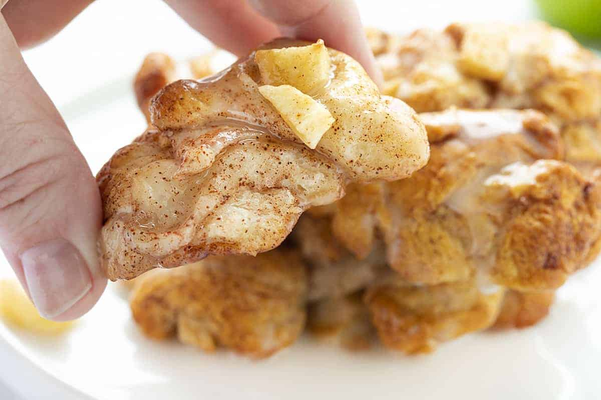 Hand holding Baked Apple Fritter showing the inside