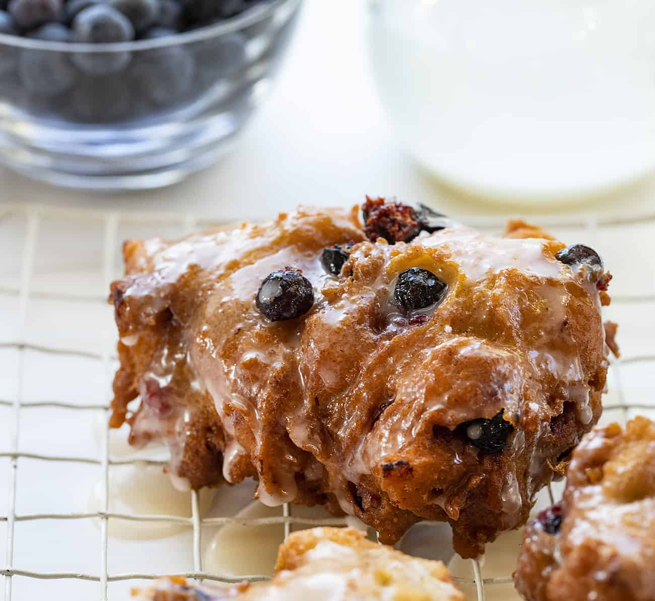 One Fresh Blueberry Fritter on Rack with Blueberries and Glaze