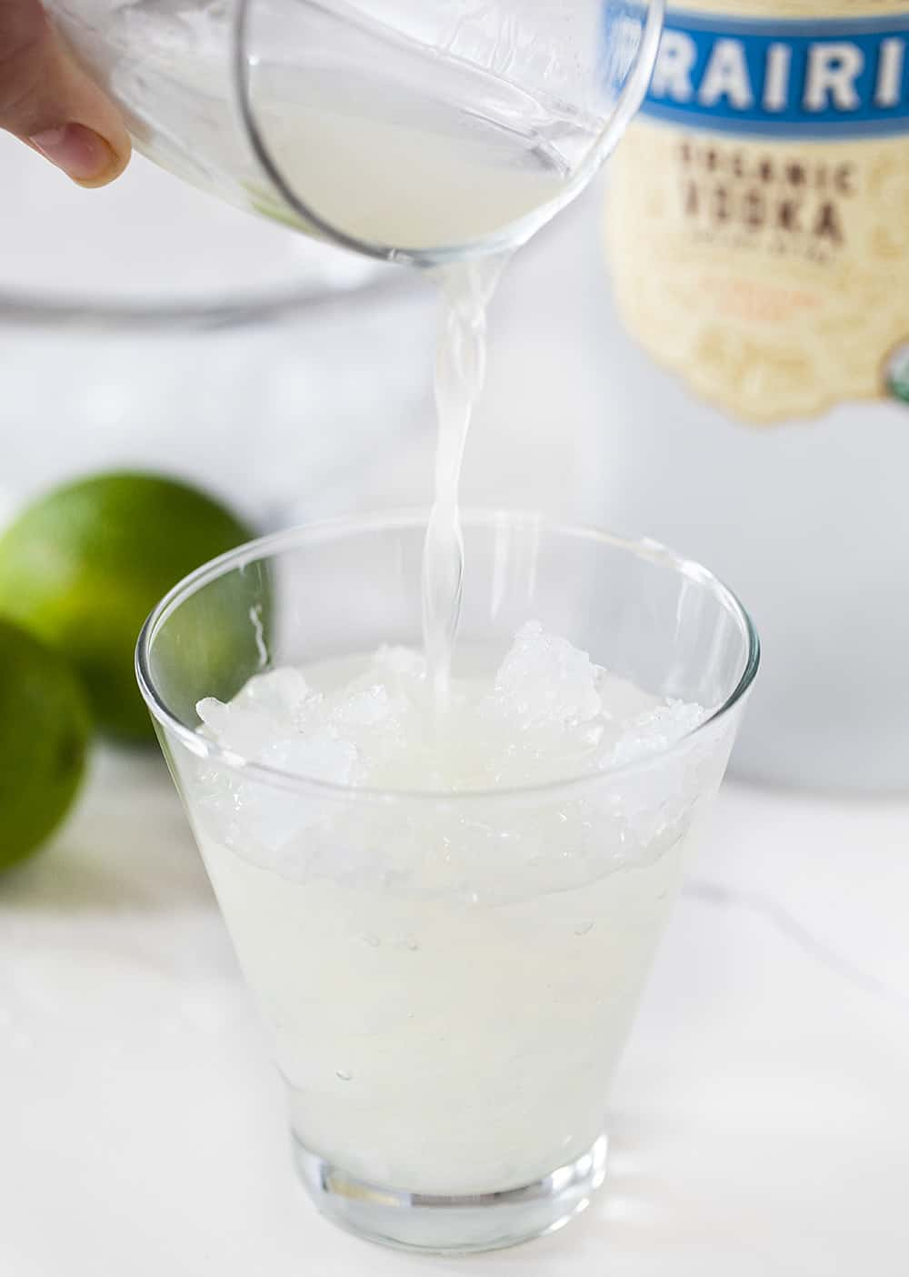 Pouring juice to Vodka Gimlet in cup of ice
