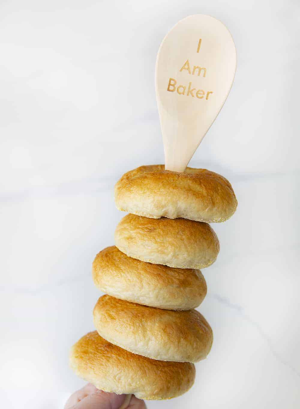 "Plain Bagels on the Handle of a Wooden Spoon with ""i am baker"" written on the spoon"