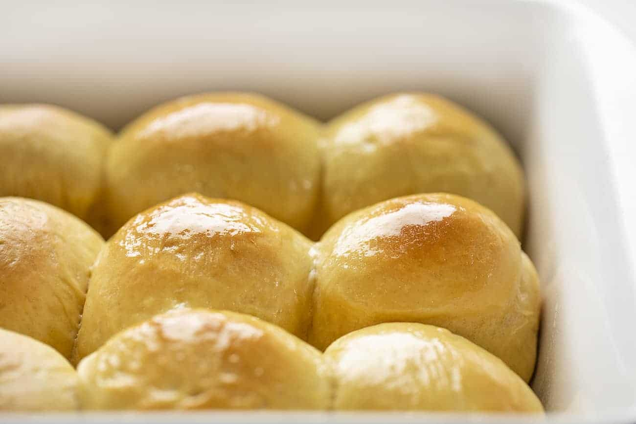 Side View of Pan of Baked Hawaiian Dinner Rolls with Butter