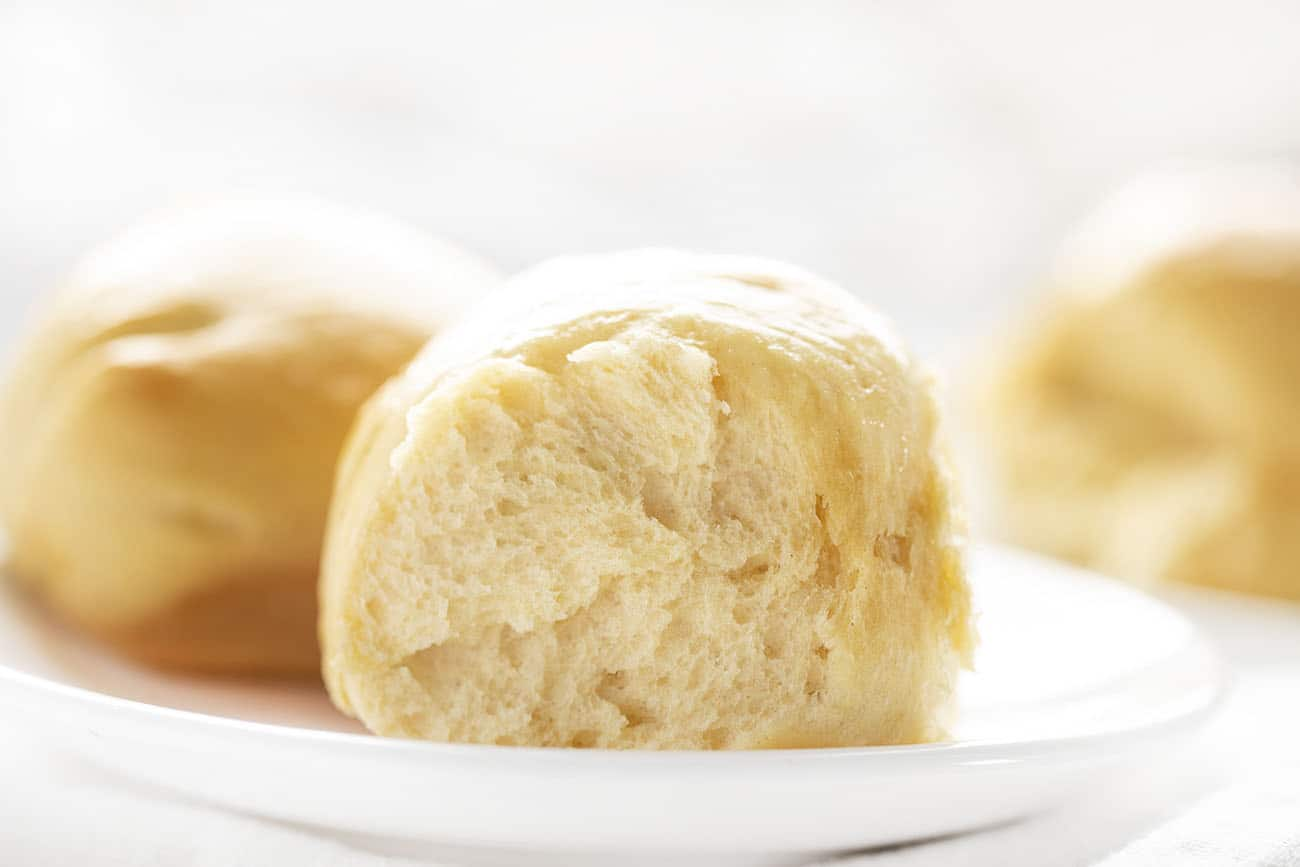 Hawaiian Dinner Rolls on White Plate with Rolls in Background