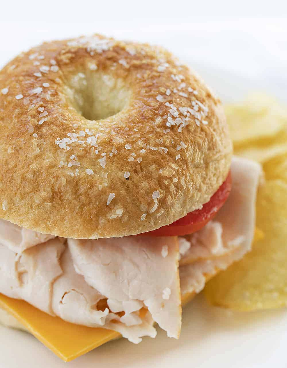 Salt Bagel Sandwich with turkey and tomato next to Chips on white plate