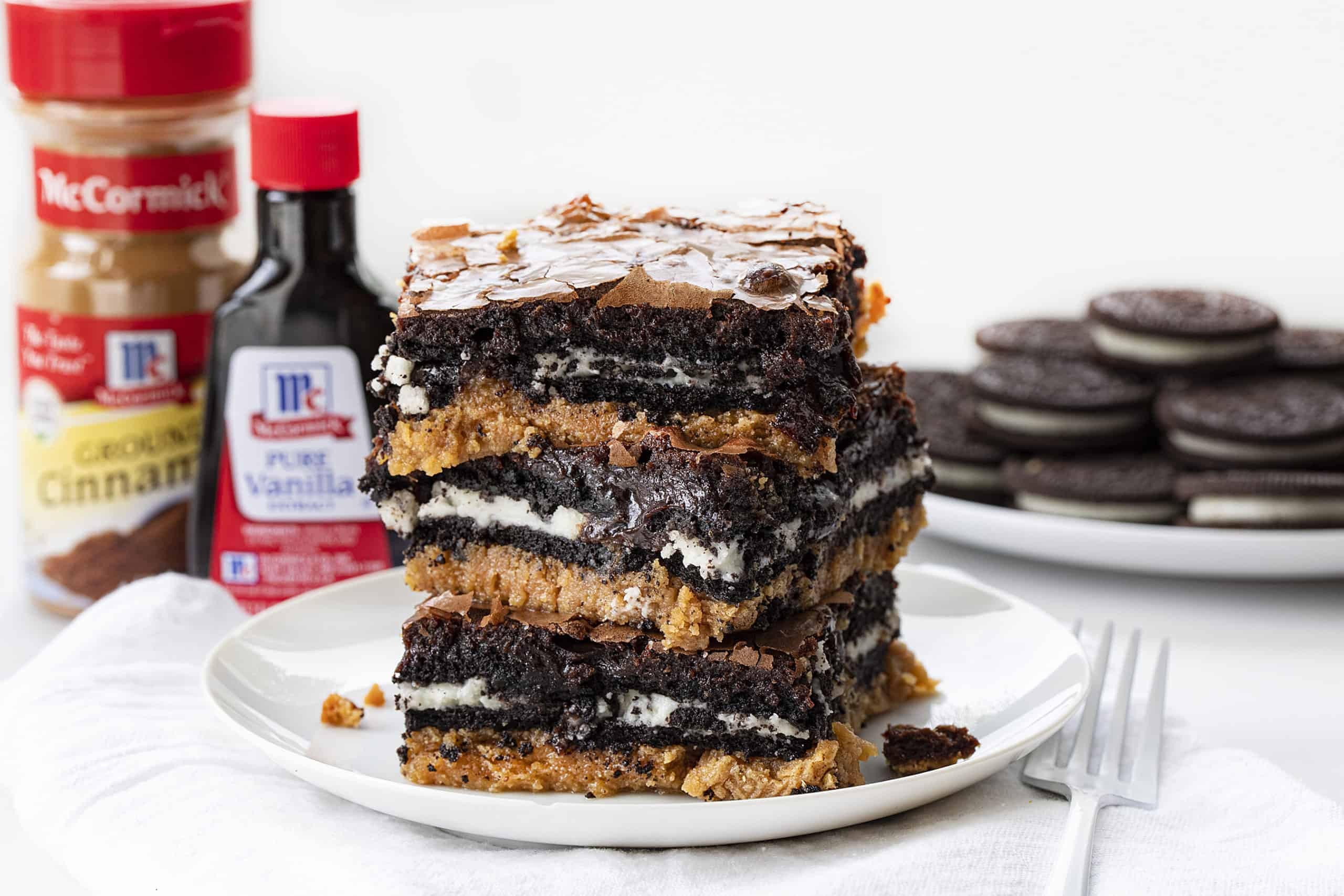 Stack of Peanut Butter Slutty Brownies with Oreos and Vanilla and Cinnamon in the Background