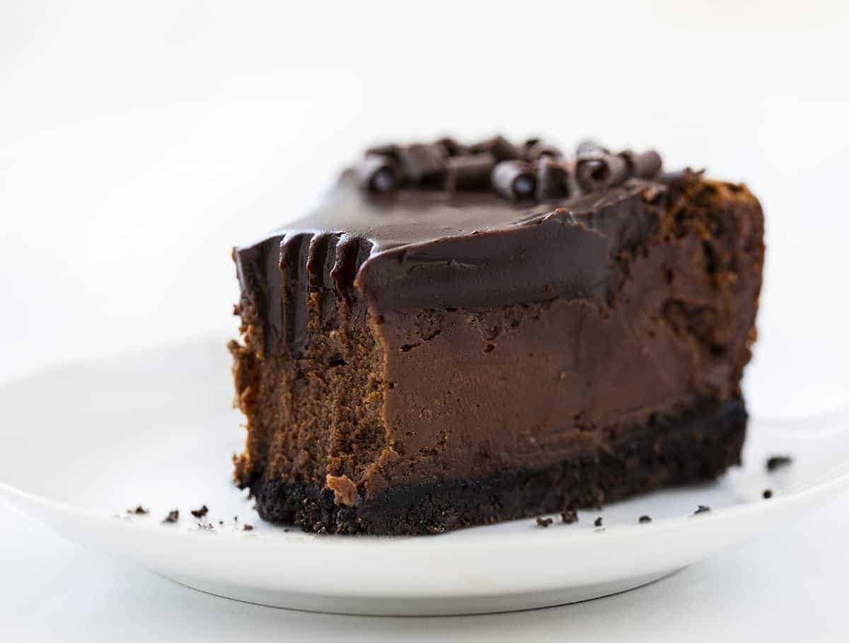 Piece of Chocolate Cheesecake with Bite Removed from the Tip on a White Plate